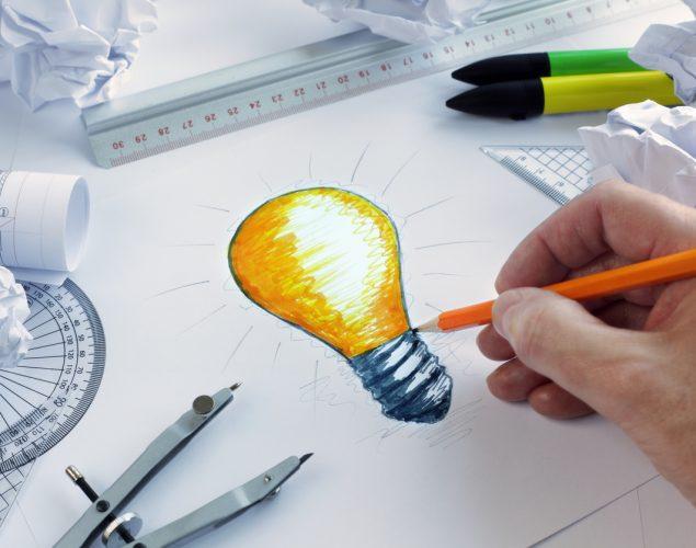 Diseñador dibujando una bombilla. Concepto: Publicidad creativa para tu pequeña empresa