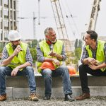 Three construction workers taking a lunch break in construction site. Concept: Hiring undocumented immigrants