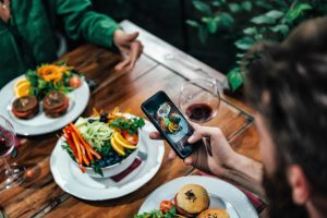 Man Photographing Food In A Restaurant. Concept: Social media for restaurants