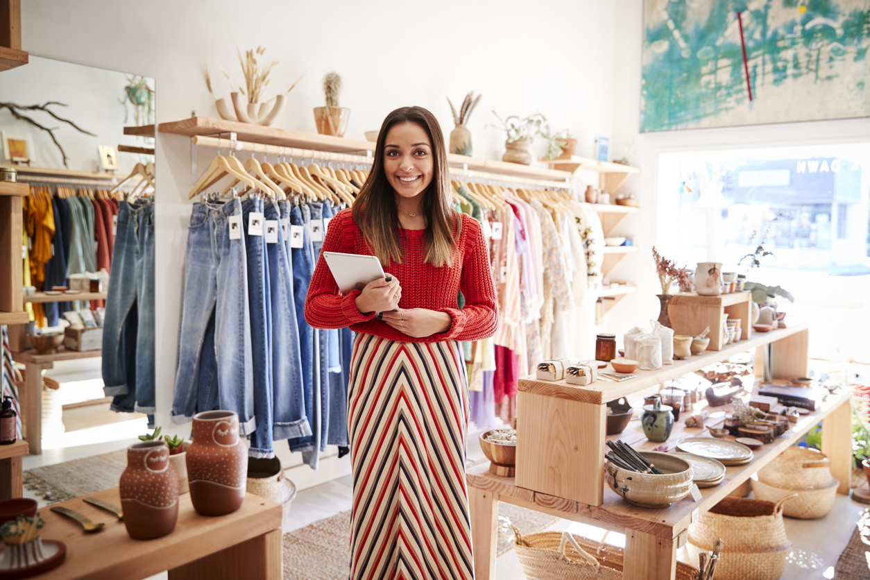 Female Business Owner Of Clothing And Gift Store With Digital Tablet. Concept: empowering women