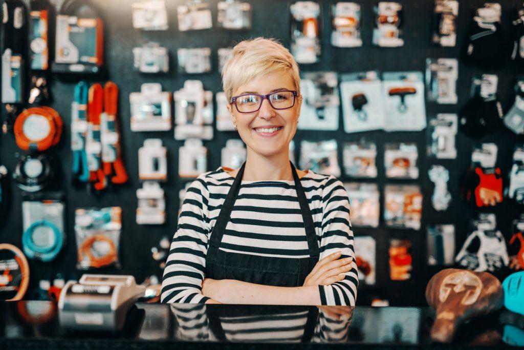 Mujer empresaria en tienda de artcículos de bicicleta, tras mostrador. Concepto: mujeres empresarias.