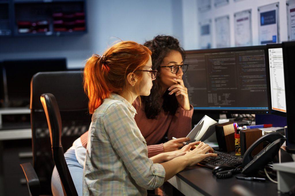 Dos programadoras trabajando en computadora. Concepto: Cómo proteger tu pequeña empresa de ataques de hackers .