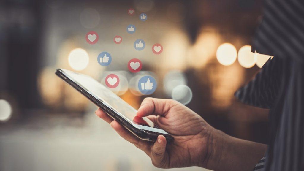 Mano usando smartphone, redes sociales.