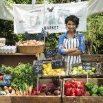 Agricultora local vendiendo productos orgánicos en un farmers market.