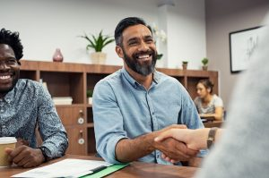 Two business people shaking hands while sitting in meeting room. Middle eastern businessman shake hands to businesswoman. Portrait of happy smiling latin man signing off deal with an handshake. Concept: small business grants