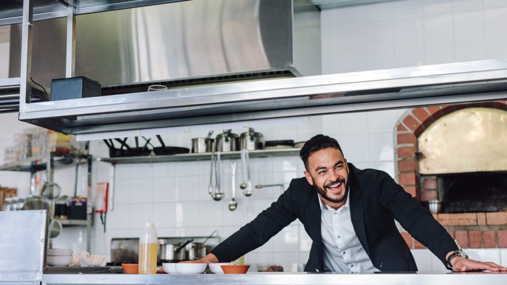 Happy young restaurant owner standing at kitchen counter looking away and smiling. Caucasian businessman in commercial kitchen. concept: small business grants