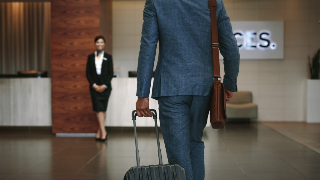 Businessman carrying suitcase while walking in hotel lobby. Business traveler arriving at hotel with female receptionist standing in background for welcoming. Concept: business insurance