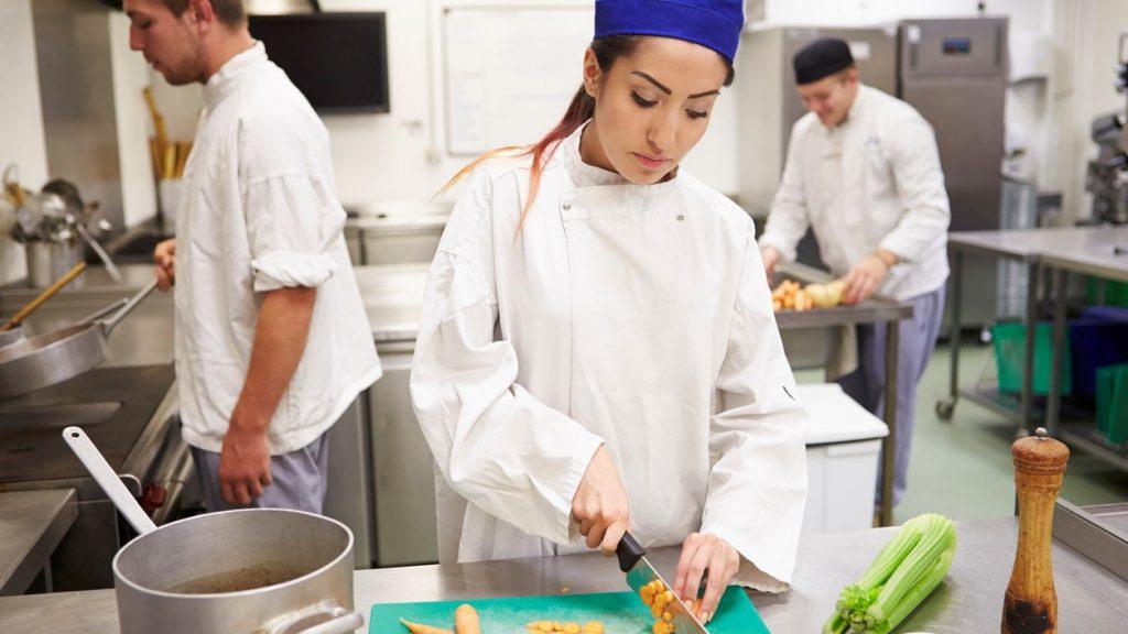 Catering, restaurante, chef, cocinera, cortando vegetales. Concept: seguro