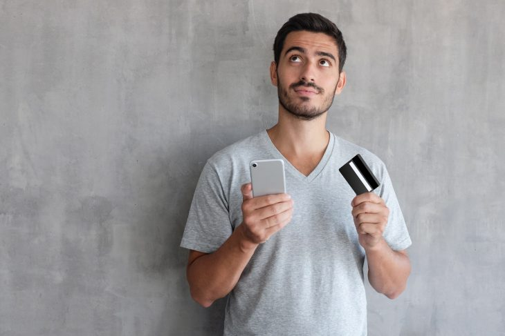 Young handsome man thinking about online shopping , wearing gray t shirt, standing against textured wall with copy space, holding credit card and cell phone. concept: Amazon credit builder card