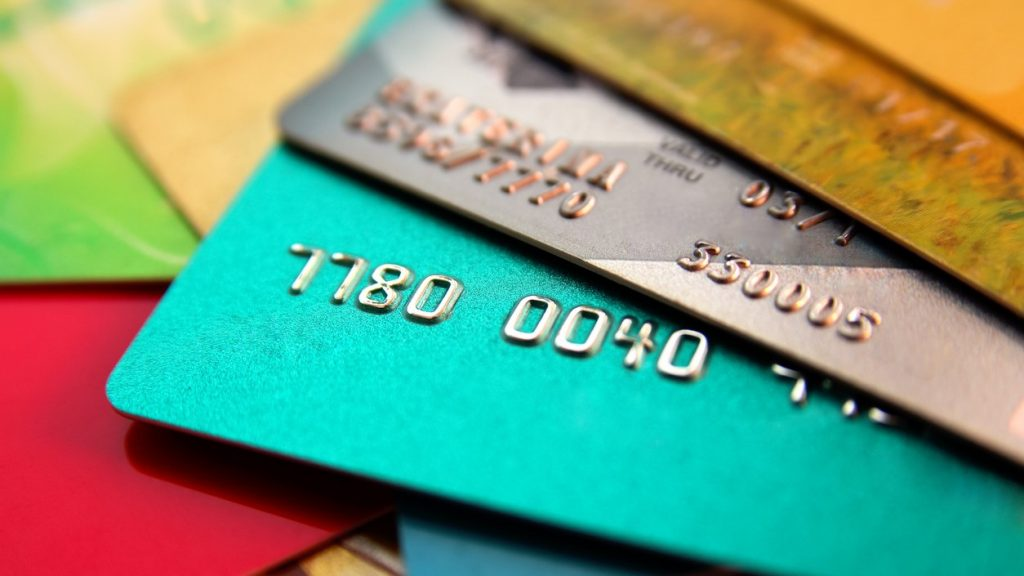stack of multicolored credit cards, close up view with selective focus. Concept: amazon credit builder card