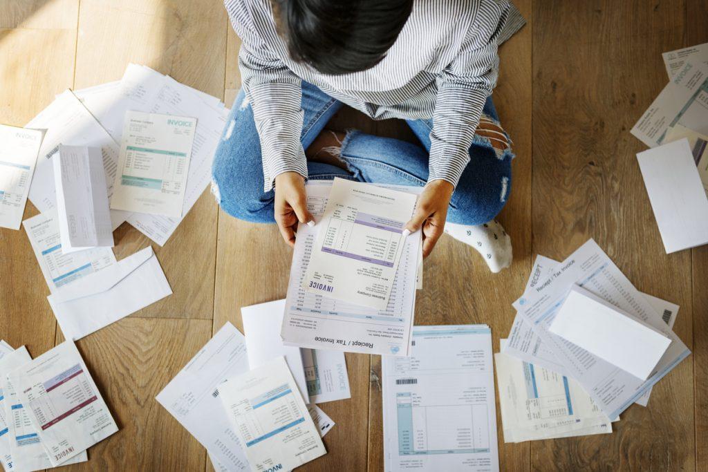 Mujer con múltiples facturas y deudas dispersas en el suelo. Concepto: Préstamos de consolidación de deuda