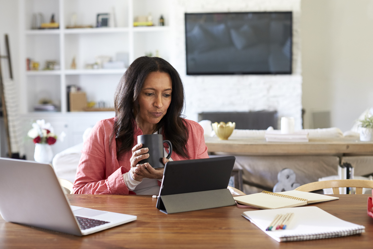 Middle aged woman sitting at a table reading using a tablet computer, holding a cup, front view. Concept: Apply for a business loan
