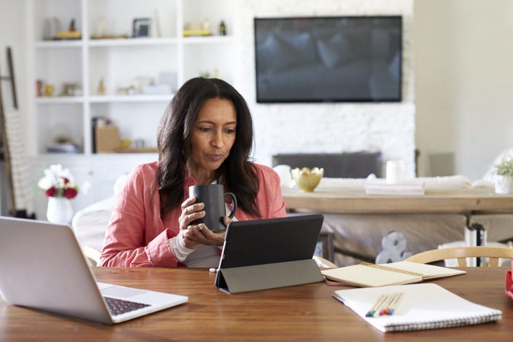 Mujer sentada frente a un escritorio leyendo y usando la computadora. Concept: préstamo