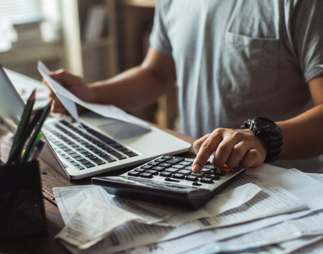 Man in front of computer calculating costs using calculator. Concept: debt consolidation loan