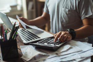 Hombre frente a computadora y usando calculadora. Concepto: Consolidación de deuda