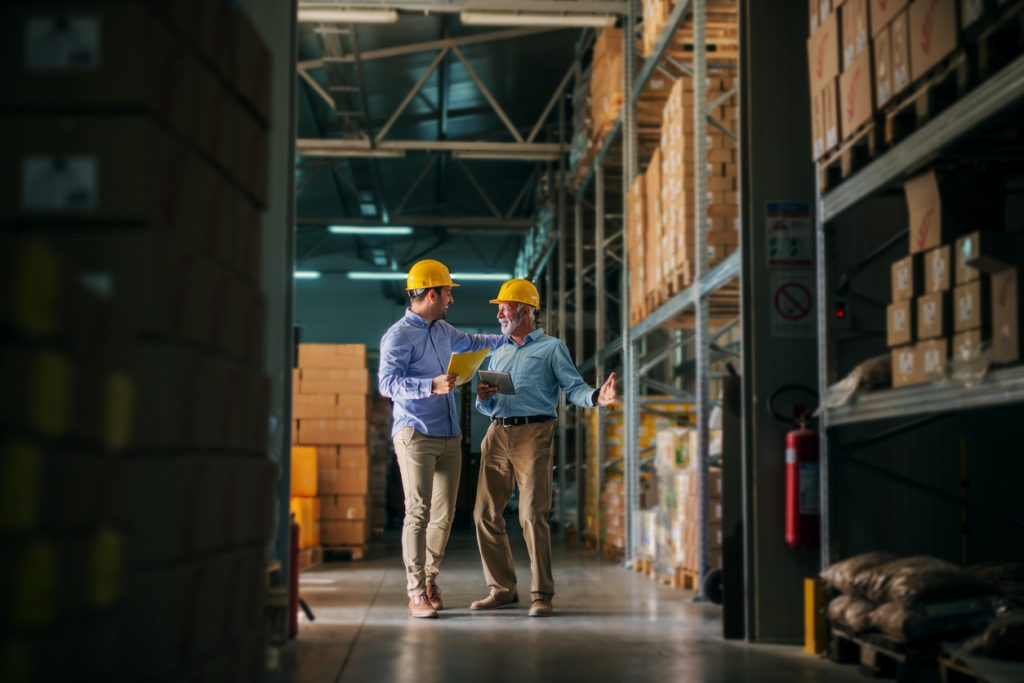 Picture of two business man standing in warehouse with helmets on their heads and celebrating great news about their business. Standing in big warehouse and looking happy and satisfied. Concept: inventory investment