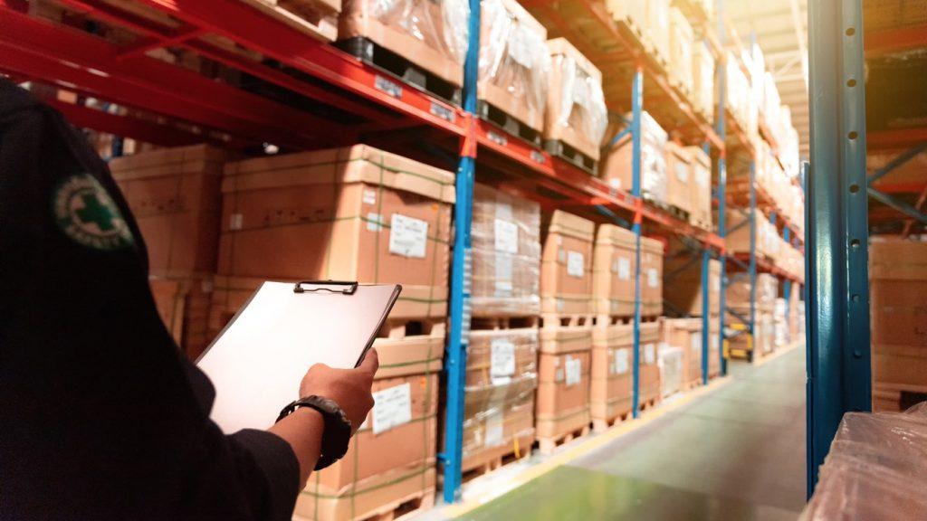 Hombre trabajando en almacen revisando stock. Concept: inversión en inventario