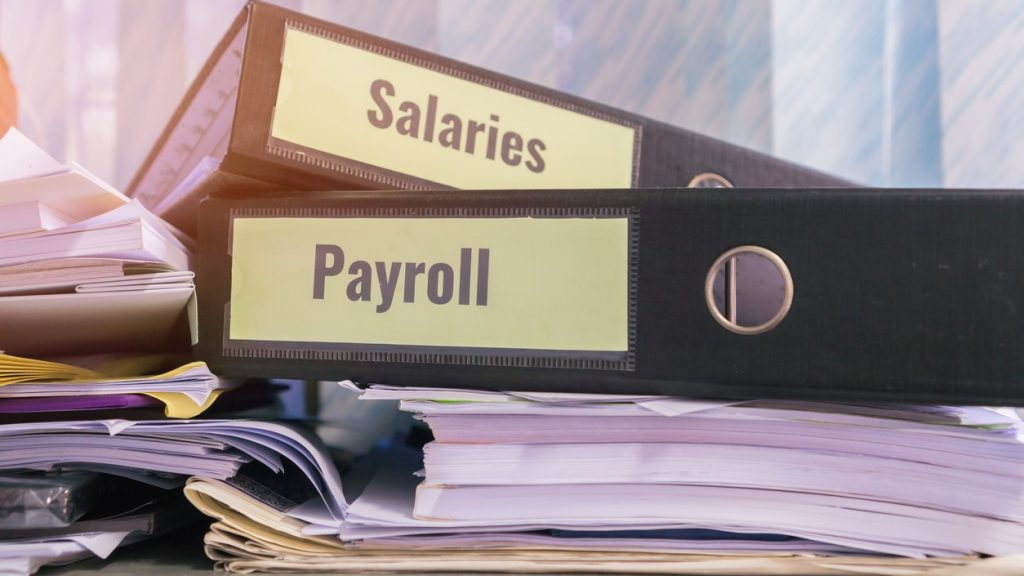 Payroll and salaries folders stack with label on black binder on paperwork documents summary report, HR-human resources business and bookkeeping accountancy concept in busy offices. Concept: salary