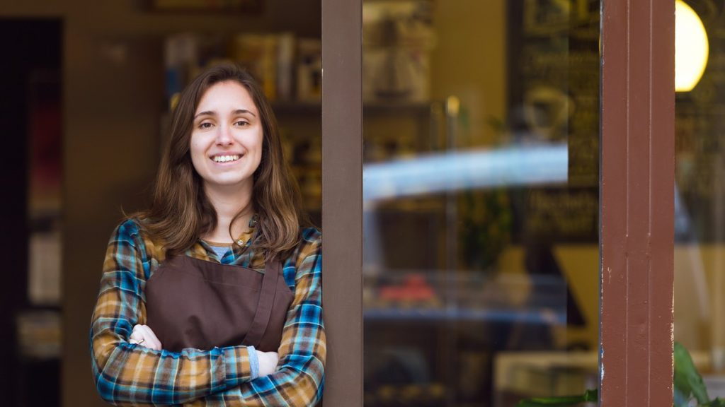 Portrait of beautiful young saleswoman looking at camera and leaning against the door frame of an organic store. Concept: salary
