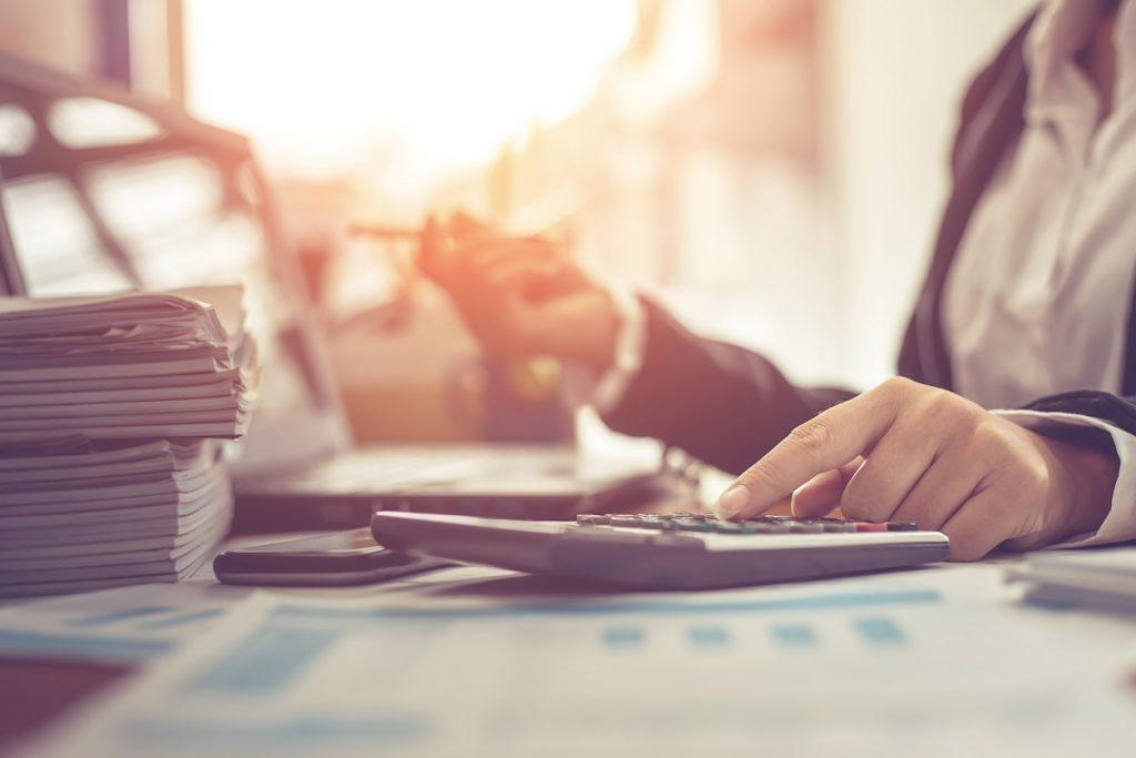 Mujer de engocios usandocalculadora y escribiendo, haciendo nota con calculadora en una oficina con laptop y documentos en su escritorio. Concept: salario