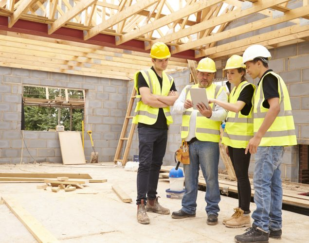 Builder On Site Looking At Digital Tablet With Apprentices. Concept: Construction company costs