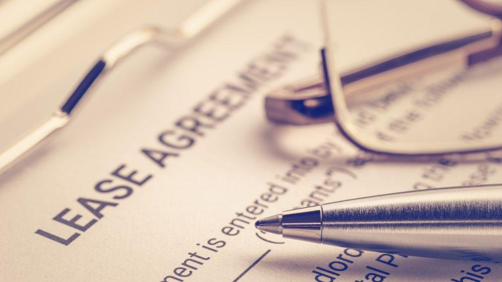 Documento legal de negocio: pluma y lentes en un contrato dearrendamiento. Concept: arrendar o comprar