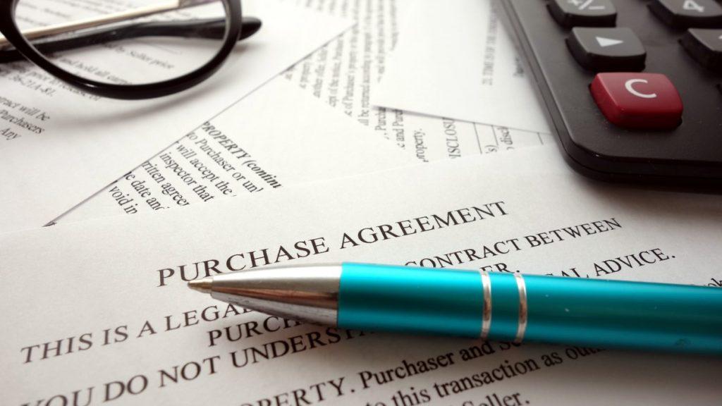 Contrato de compra en un escritorio, lentes y pluma. Concept: arrendar o comprar