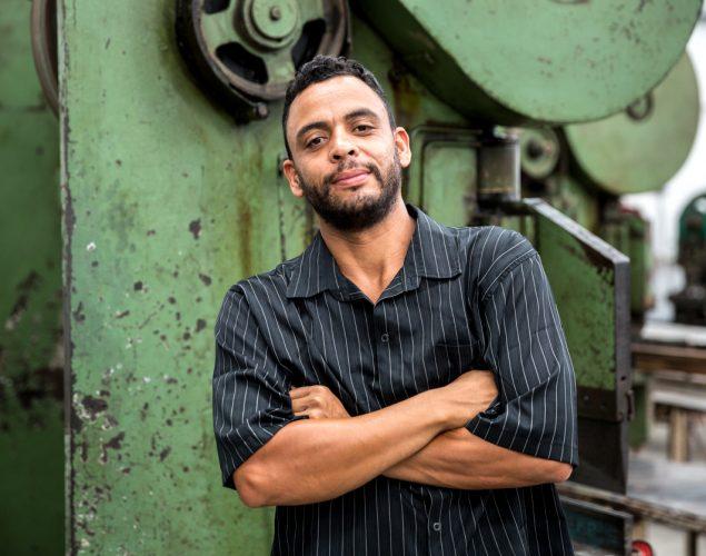 Trabajador latino frente a maquinaria en una fábrica. Concepto: leyes de inmigración.