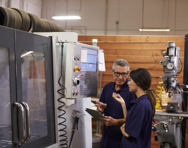 Engineer Training Female Apprentice On CNC Machine. Concept: leasing vs buying