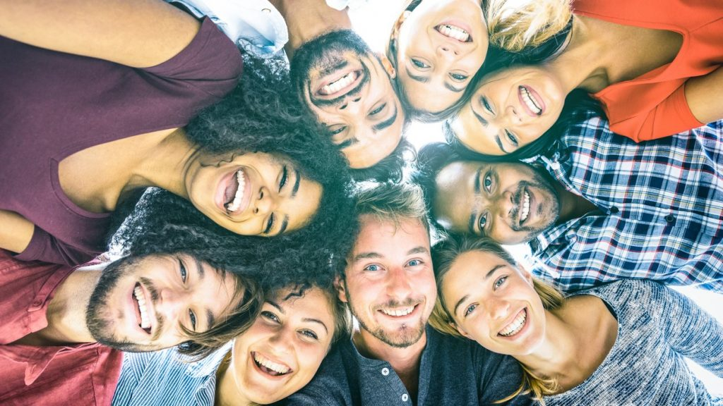 Multiracial best friends millennials taking selfie outdoors with back lighting - Happy youth friendship concept against racism with international young people having fun together - Azure filter tone. Concept: minority business certification