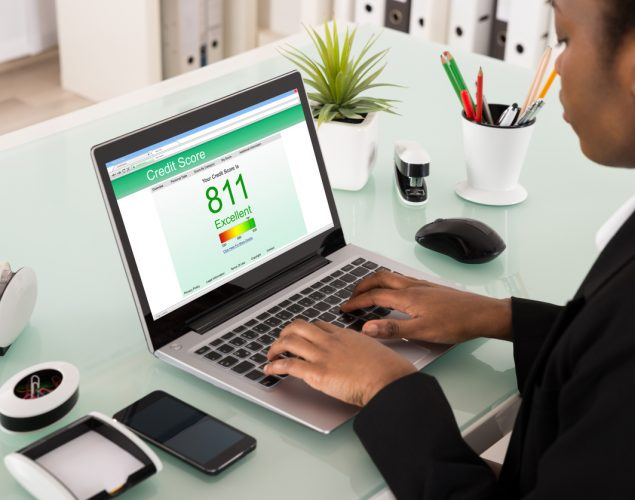 Businesswoman Checking FICO Score On Laptop At Office
