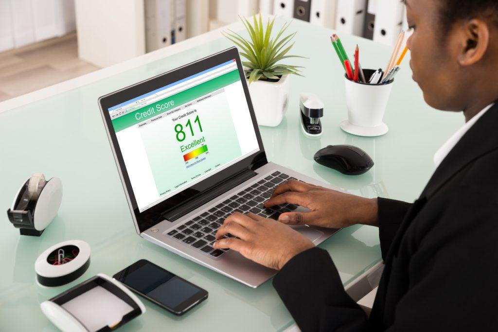 Mujer de negocios consultando su puntaje FICO en computadora.