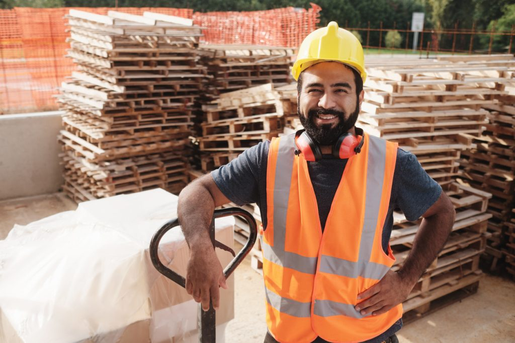 Skilled people working in construction site. Hispanic man at work in new house. Portrait of happy latino worker using manual forklift to move hardware and smiling at camera concept: construction credit cards