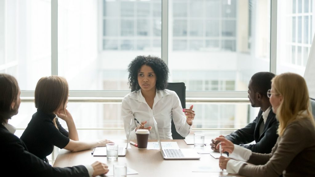Black female boss leading corporate multiracial team meeting talking to diverse businesspeople, african american woman executive discussing project plan at group multi-ethnic briefing in boardroom. concept: WOSB