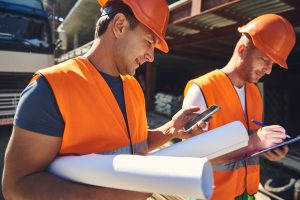 Two construction workers in construction site with blueprints and cellphone. Concept: Store credit cards for construction companies