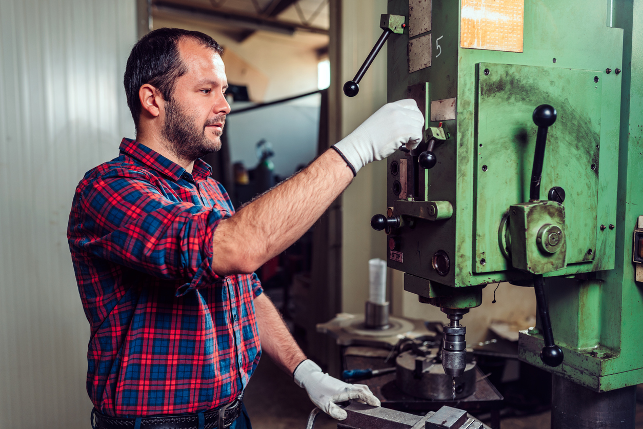 Worker using drill press in factory. Concept: Trump import tariffs