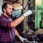 Trabajador usando máquina industrial en fábrica. Concepto: tarifas de importación de Trump