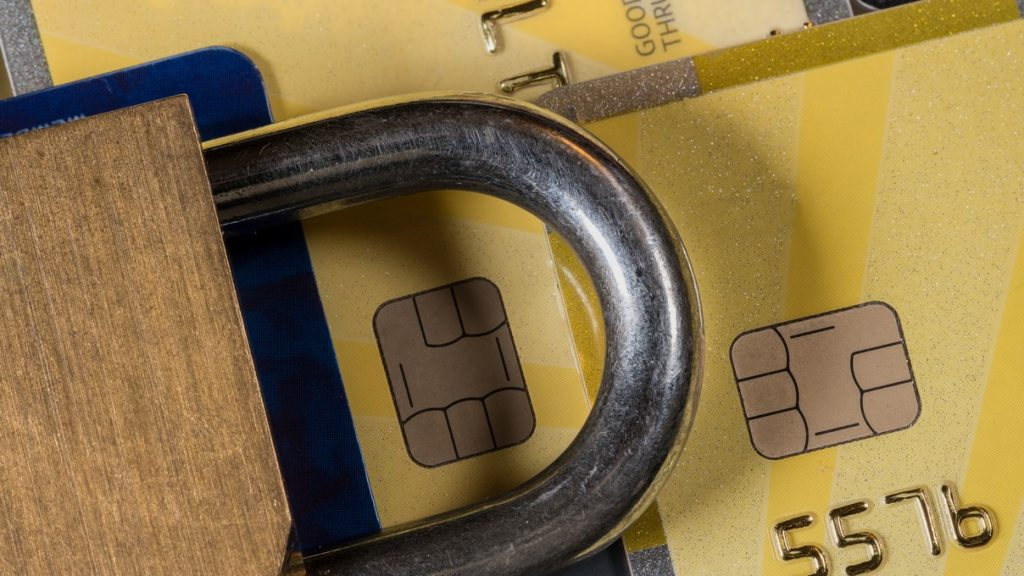 Brass padlock on credit cards with focus on electronic chip for security or credit lock. Concept: credit freeze