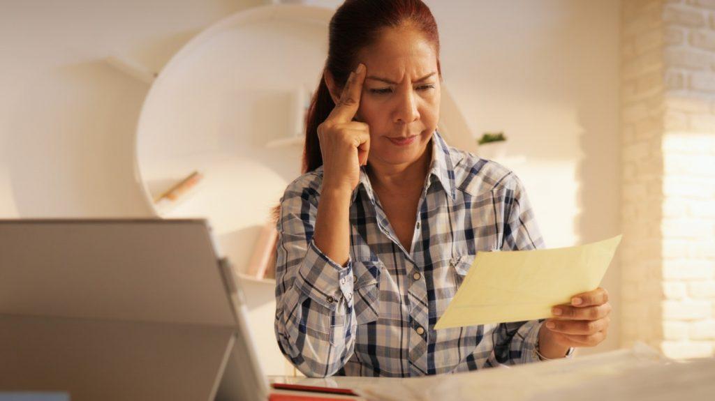 Mujer mayor, banco en línea. confusa, preocupada mirando un papel. Concept: crédito