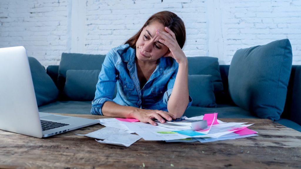 Retrato de una mujer de negocios, madre, sintiéndose estresada sobre finanzas, contaduría, con laptop y calculadora en su oficina. Concept: Recesión
