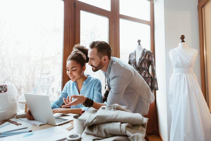 Man and woman looking at laptop in bridal dress design studio.