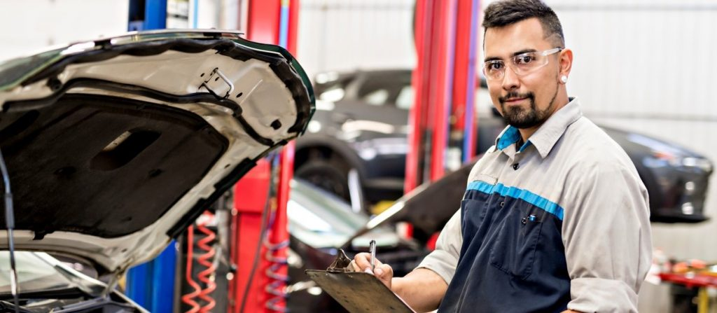 A Handsome mechanic job in uniform working on car. concept: leasing vs buying