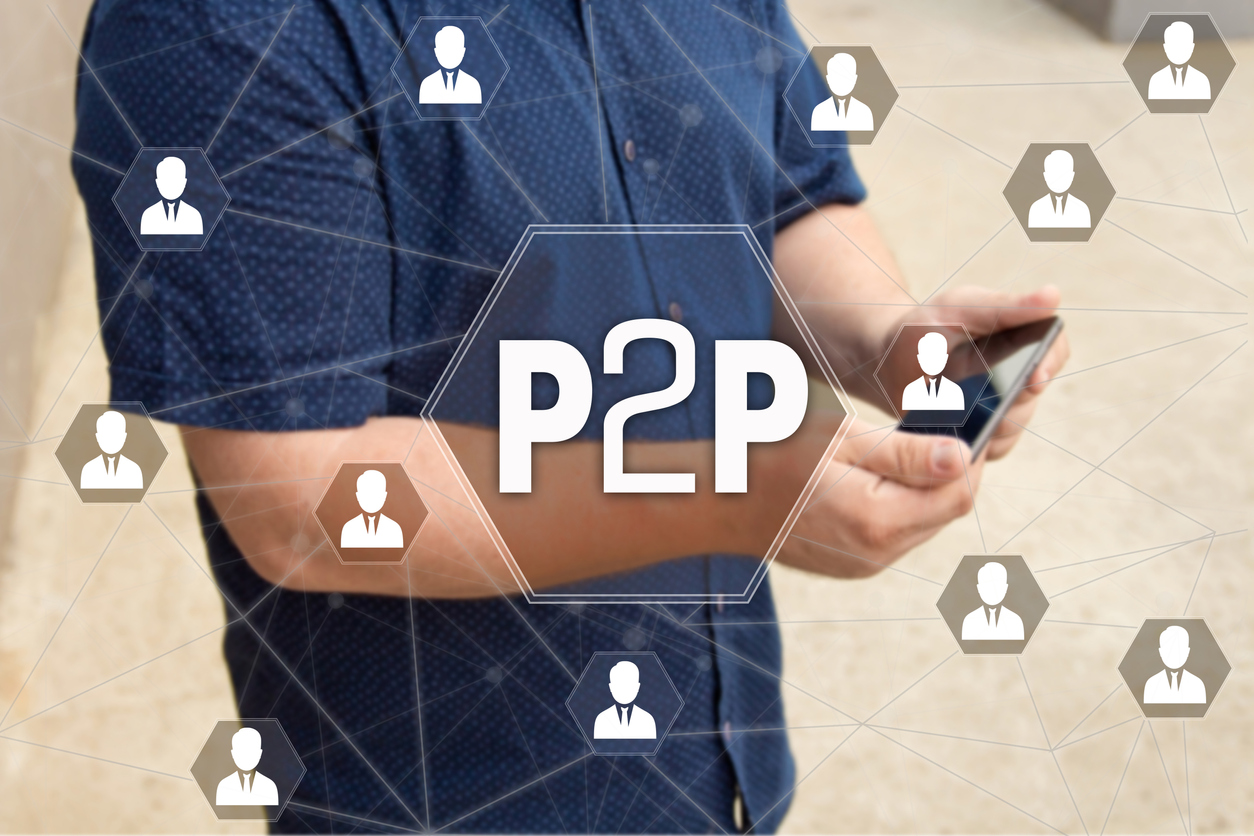 Peer-to-peer lending: P2P on the touch screen with a blur background of the businessman with the phone.
