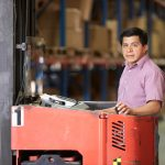 Immigrant worker driving Fork Lift Truck In Warehouse. Concept: immigration and small business