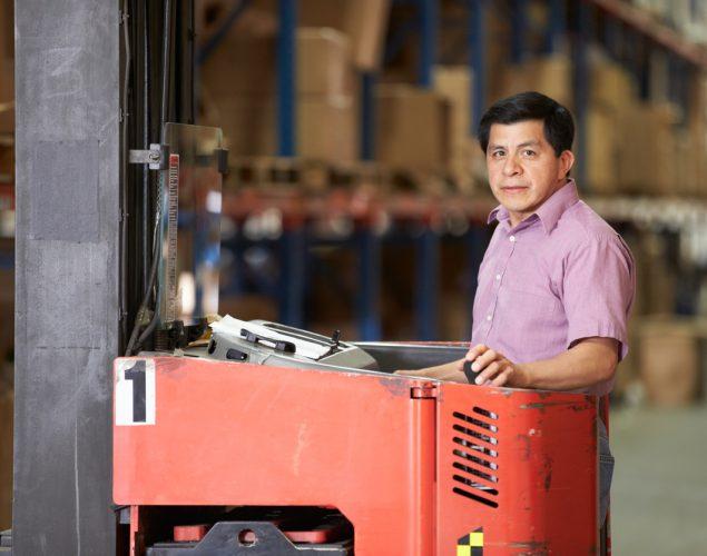 Trabajador inmigrante operando montacargas en un almacén. Concepto: inmigración y pequeñas empresas.