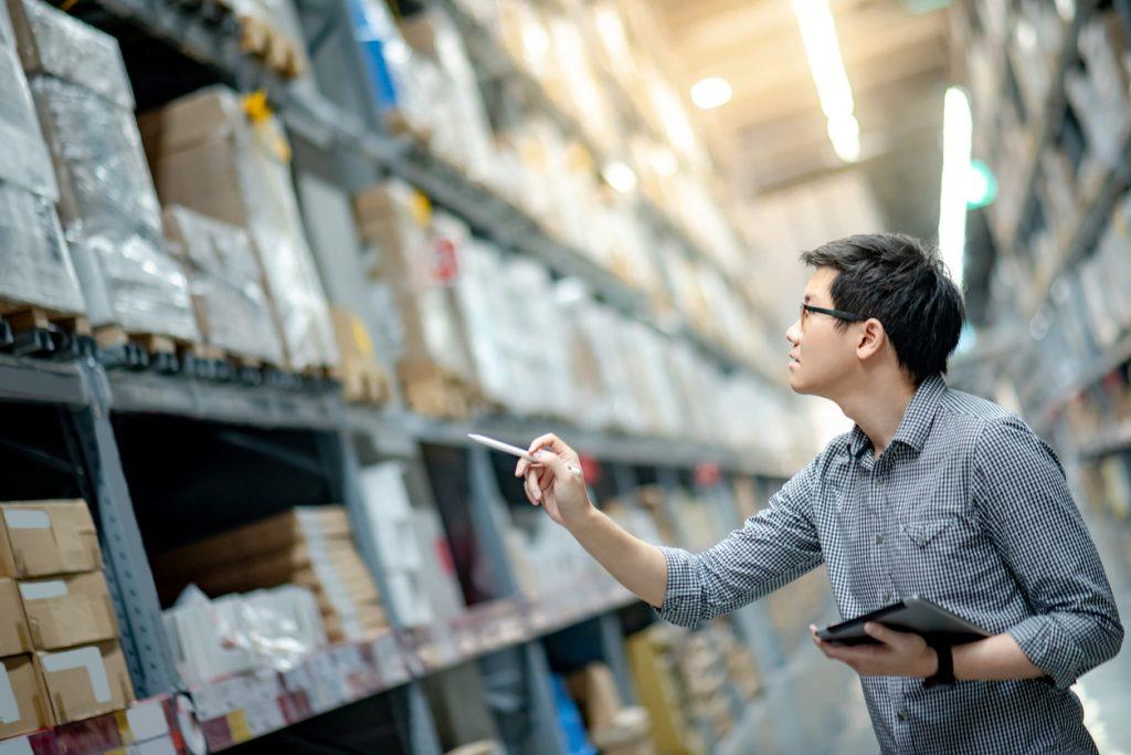Joven asiático trabajando con el inventario de una empresa, contando cajas de cartón en la bodega con una tablet. Inventario físico. Concept: gestión de inventario