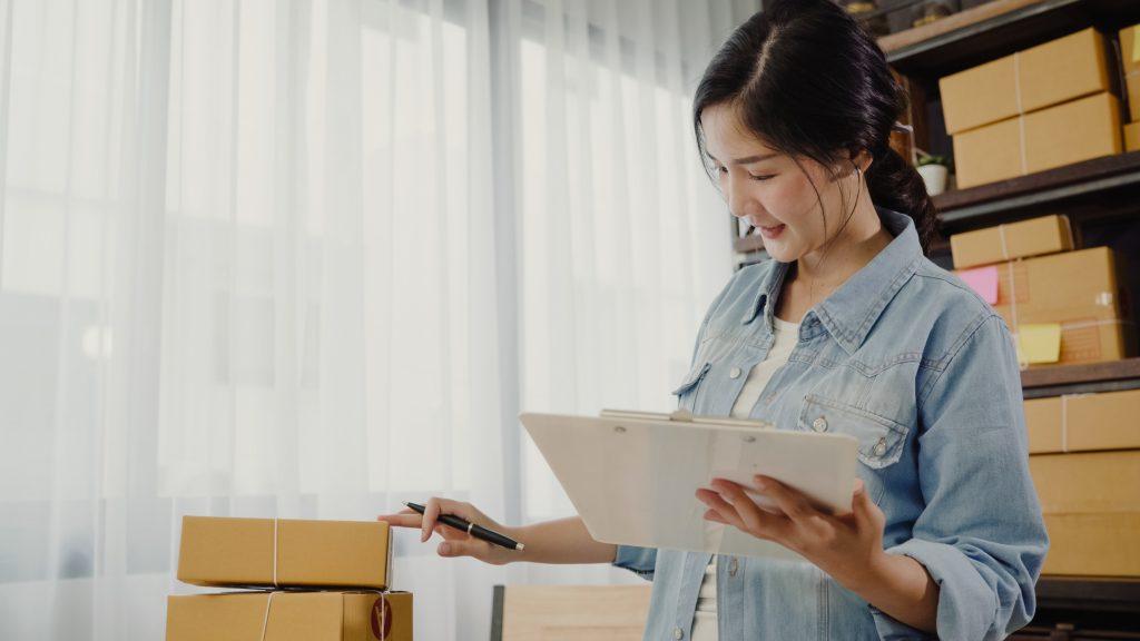 Mujer asiática joven, emprendedora, dueña de negocio, revisando stock. Concept: gestión de inventario. Business photo created by tirachardz - www.freepik.com