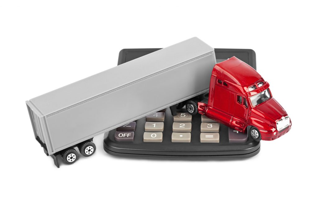 Calculator and toy truck car isolated on white background. concept: commercial vehicle