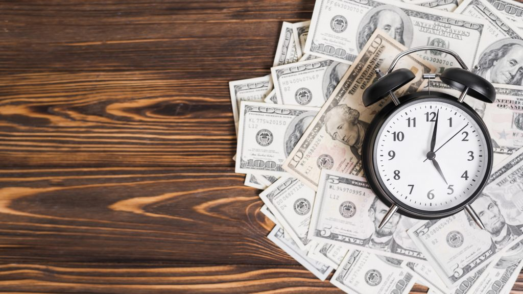Dinero, billetes, dólares sobre una mesa de madera con un reloj encima, despertador, alarma, tiempo. Concept: préstmos puente. Designed by Freepik