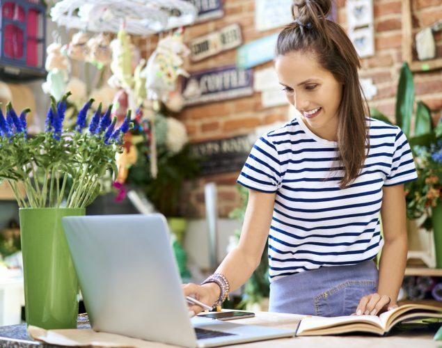 Florista trabajando en laptop y anotando en un cuaderno. Concepto: marketing de contenido.